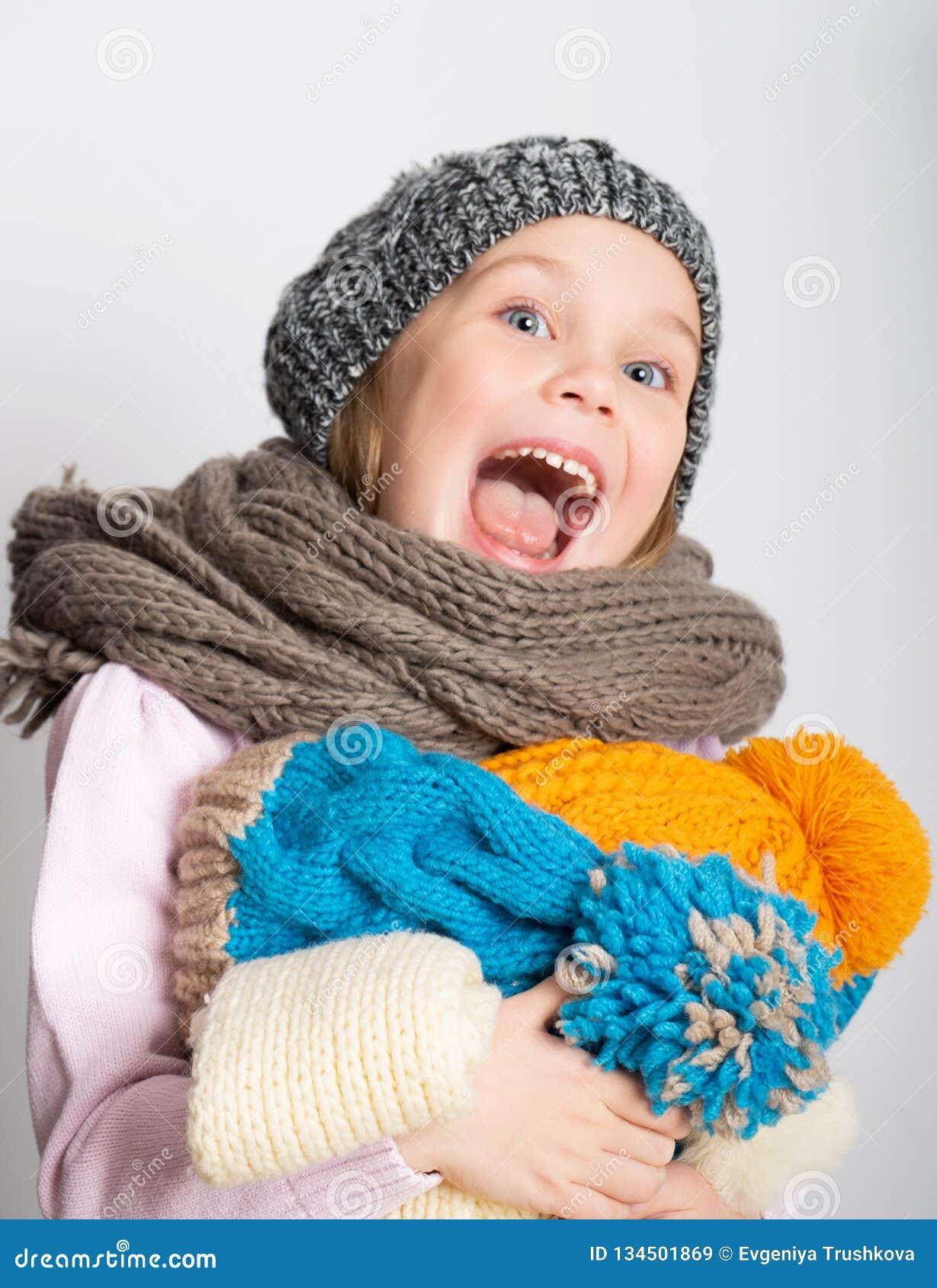Bambina che porta cappello, sciarpa tricottata e maglione, tenenti un mucchio dei cappelli,