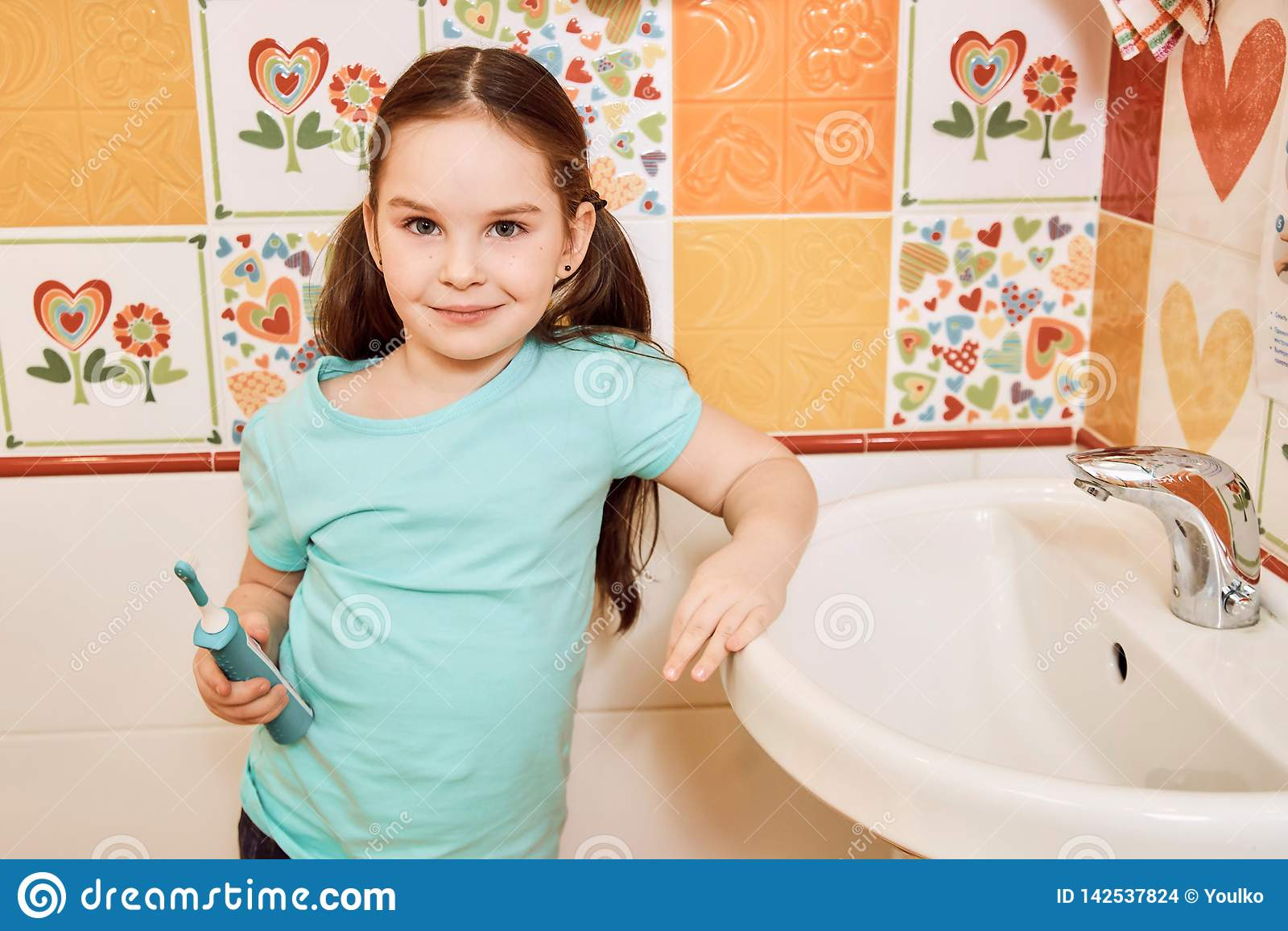 Bambina che pulisce i suoi denti nel bagno