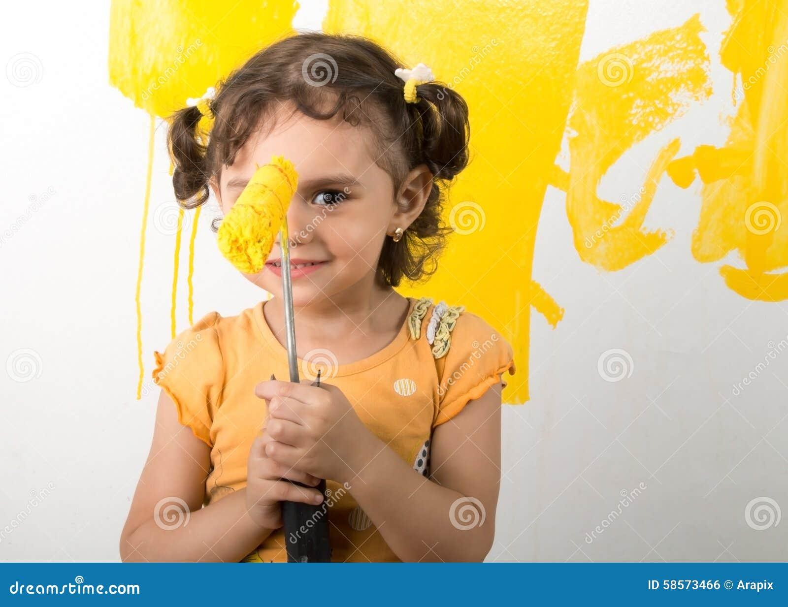 Bambina che ritiene felice mentre dipingendo parete domestica