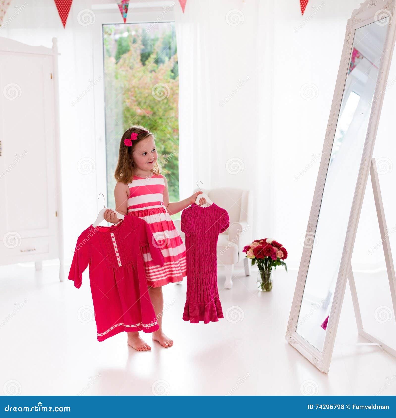 db8c72cff40e Bambina Che Sceglie I Vestiti In Camera Da Letto Bianca Fotografia ...