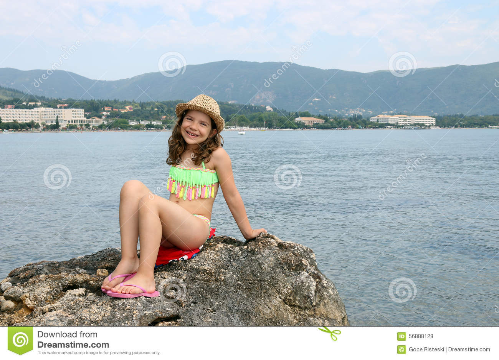 Bambina che si siede su una roccia entro le vacanze estive del mare