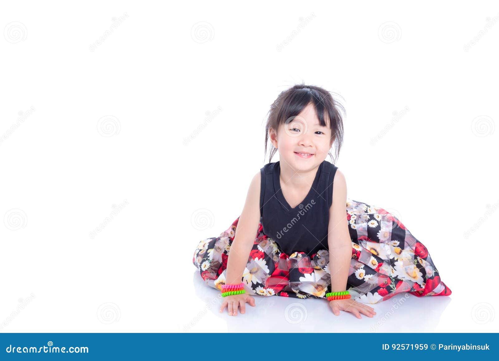 Bambina che si siede sul pavimento e sui sorrisi