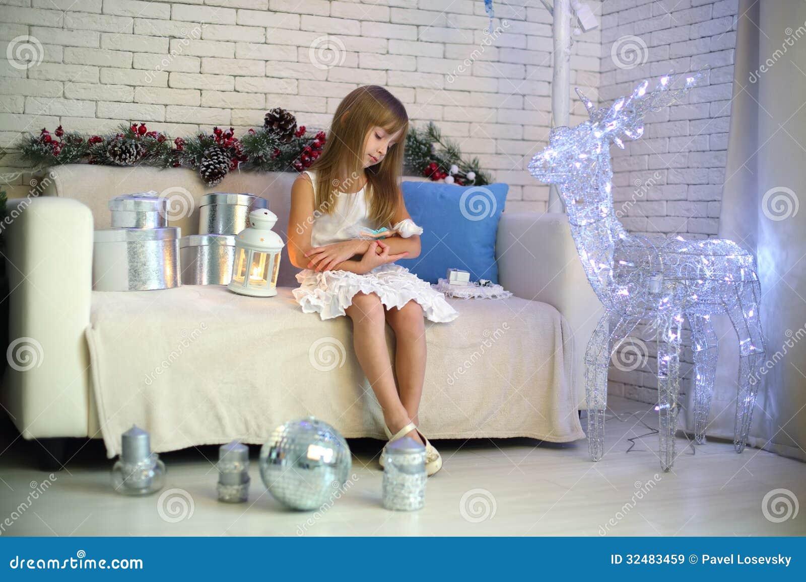 Bambina che si siede sul sofà con i regali di Natale