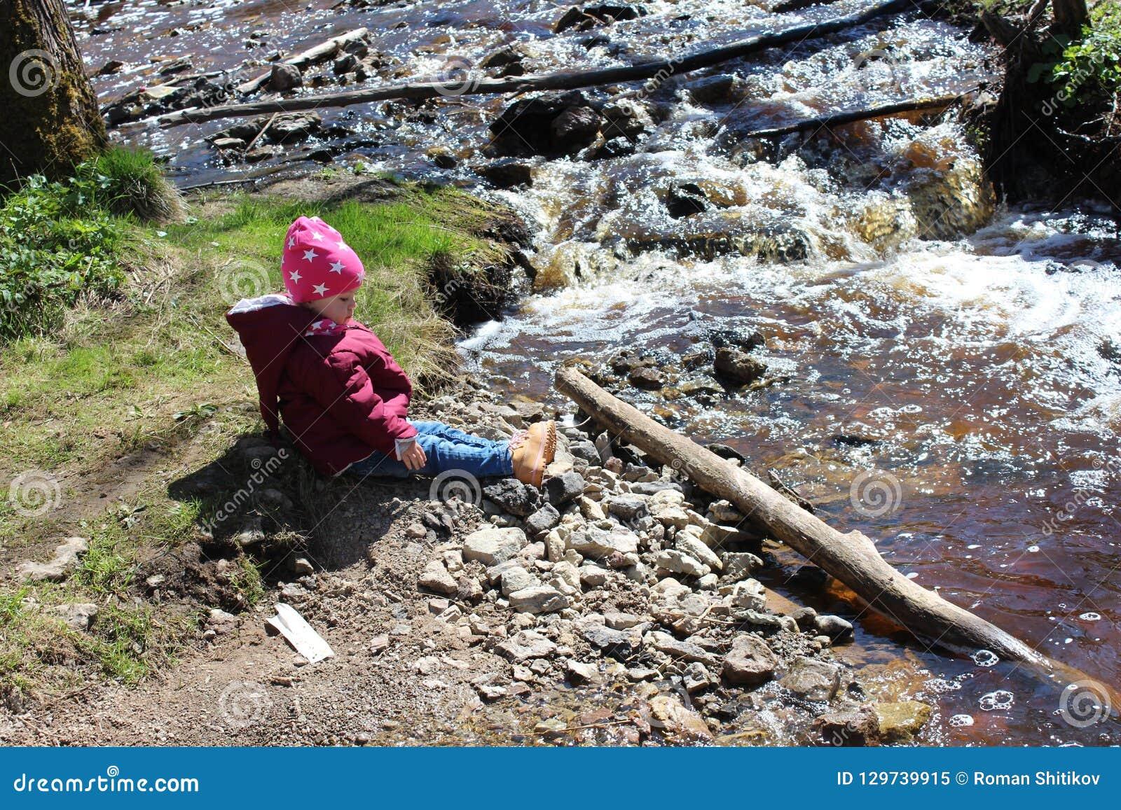 Bambina che si siede vicino ad un fiume della montagna