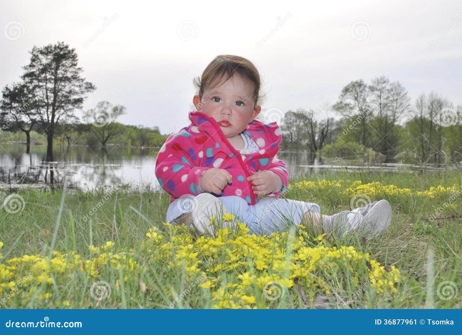 Download Bambina Che Si Siede Vicino Ad Un Lago In Fiori Gialli Immagine Stock - Immagine di bellezza, spiaggia: 36877961
