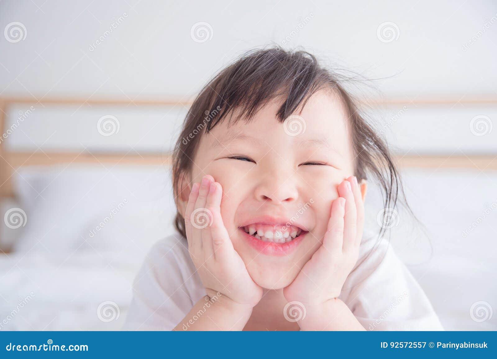 Bambina che sorride sul letto