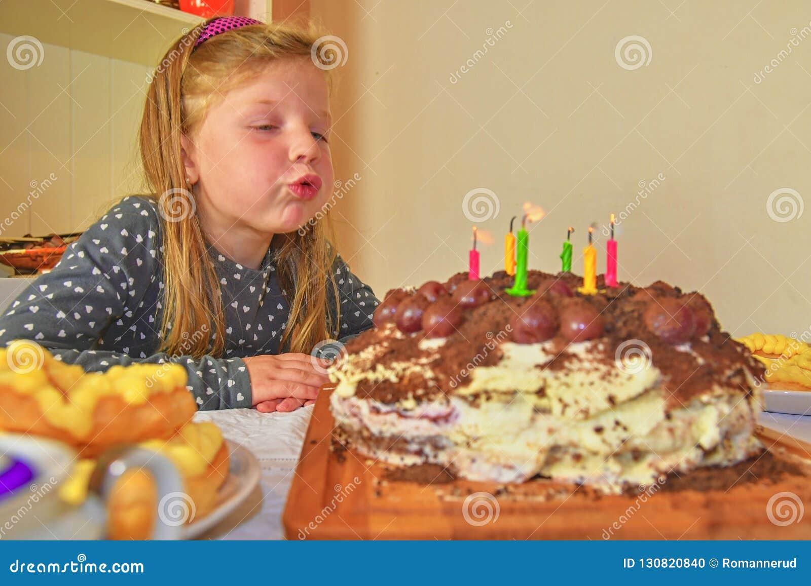 Bambina che spegne le candele sulla sua torta di compleanno Piccola ragazza che celebra i suo sei compleanni Torta di compleanno