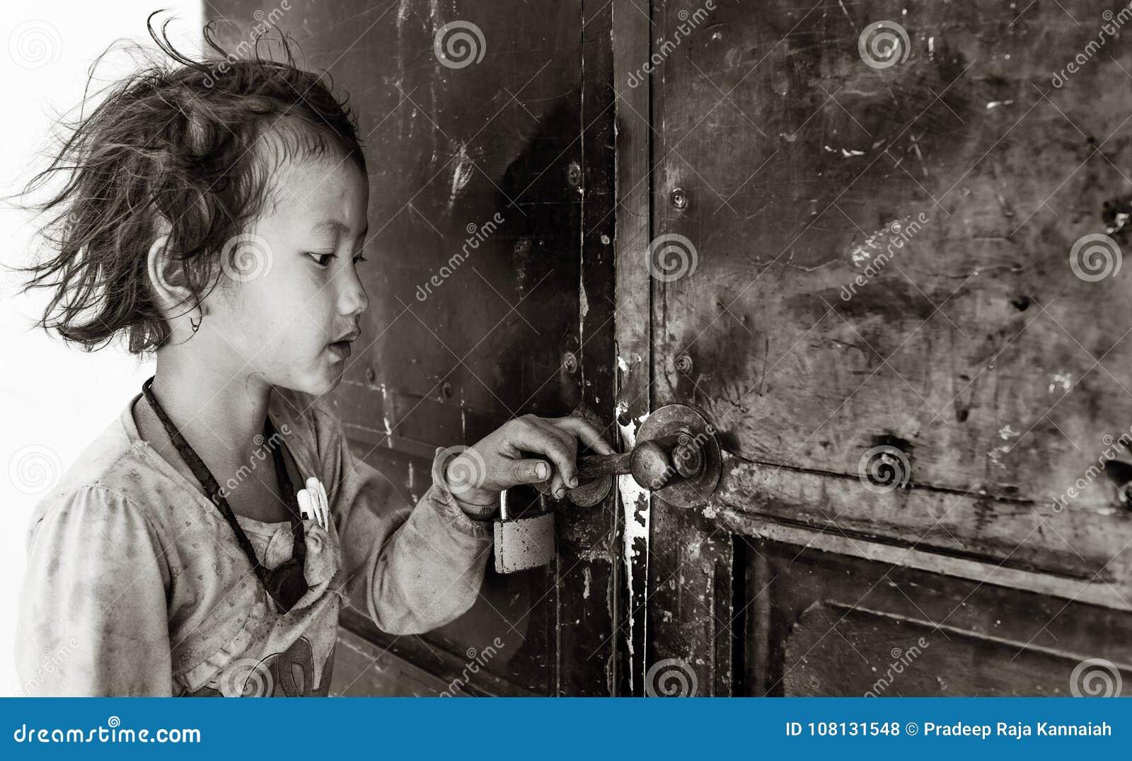 Bambina che tiene la porta dell insegnante aspettante dell aula chiusa per aprirsi, Sapa, Vietnam