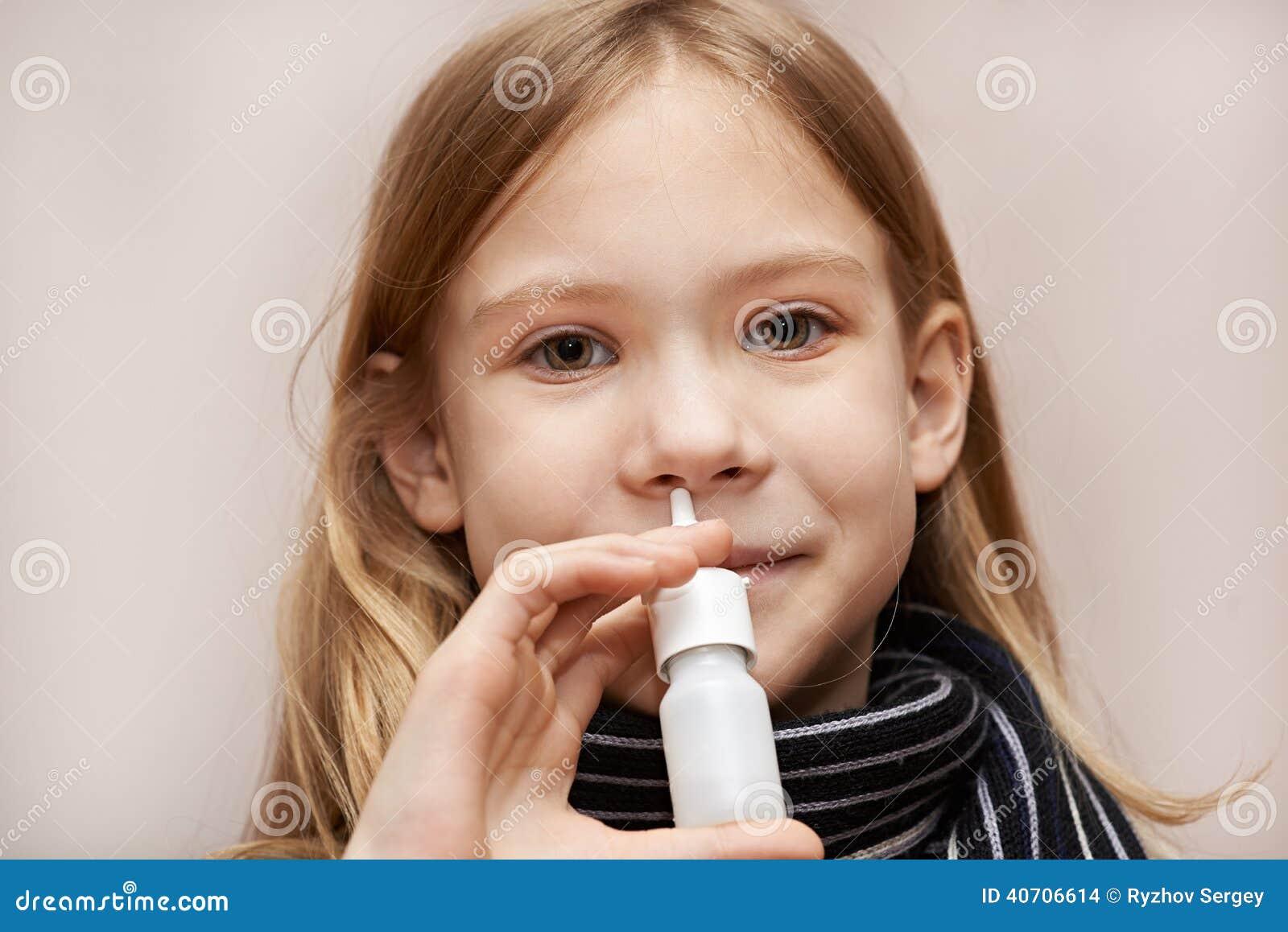 Bambina che usando le gocce nasali