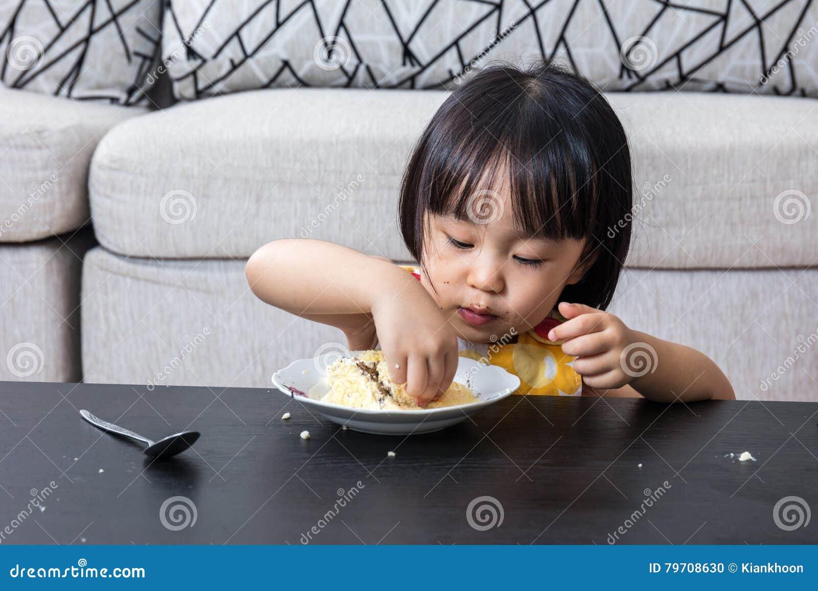 Bambina cinese asiatica che mangia la torta di formaggio di compleanno