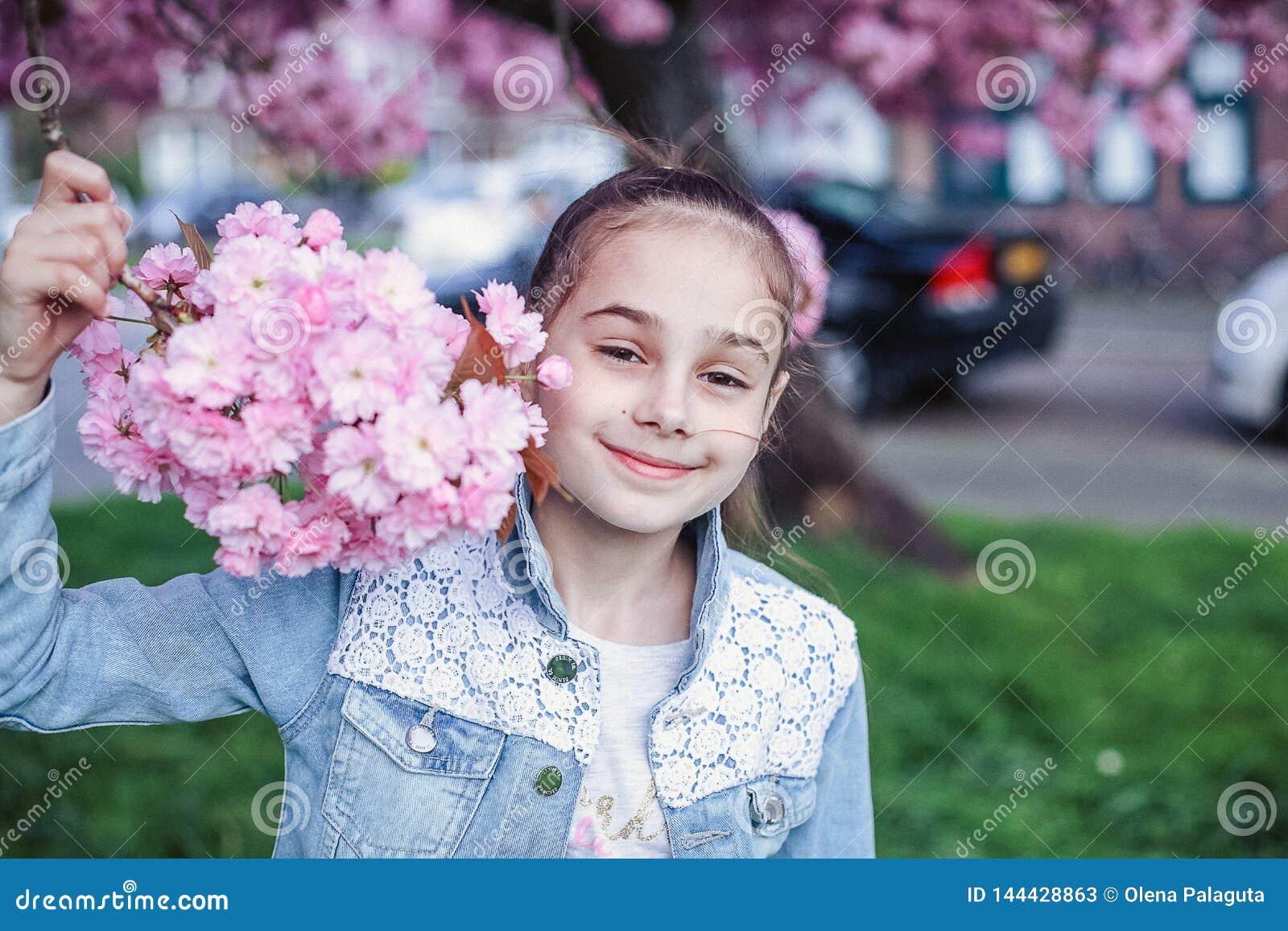 Bambina con capelli marroni in rivestimento blu del denim divertendosi nel giardino della ciliegia del fiore il bello giorno di m
