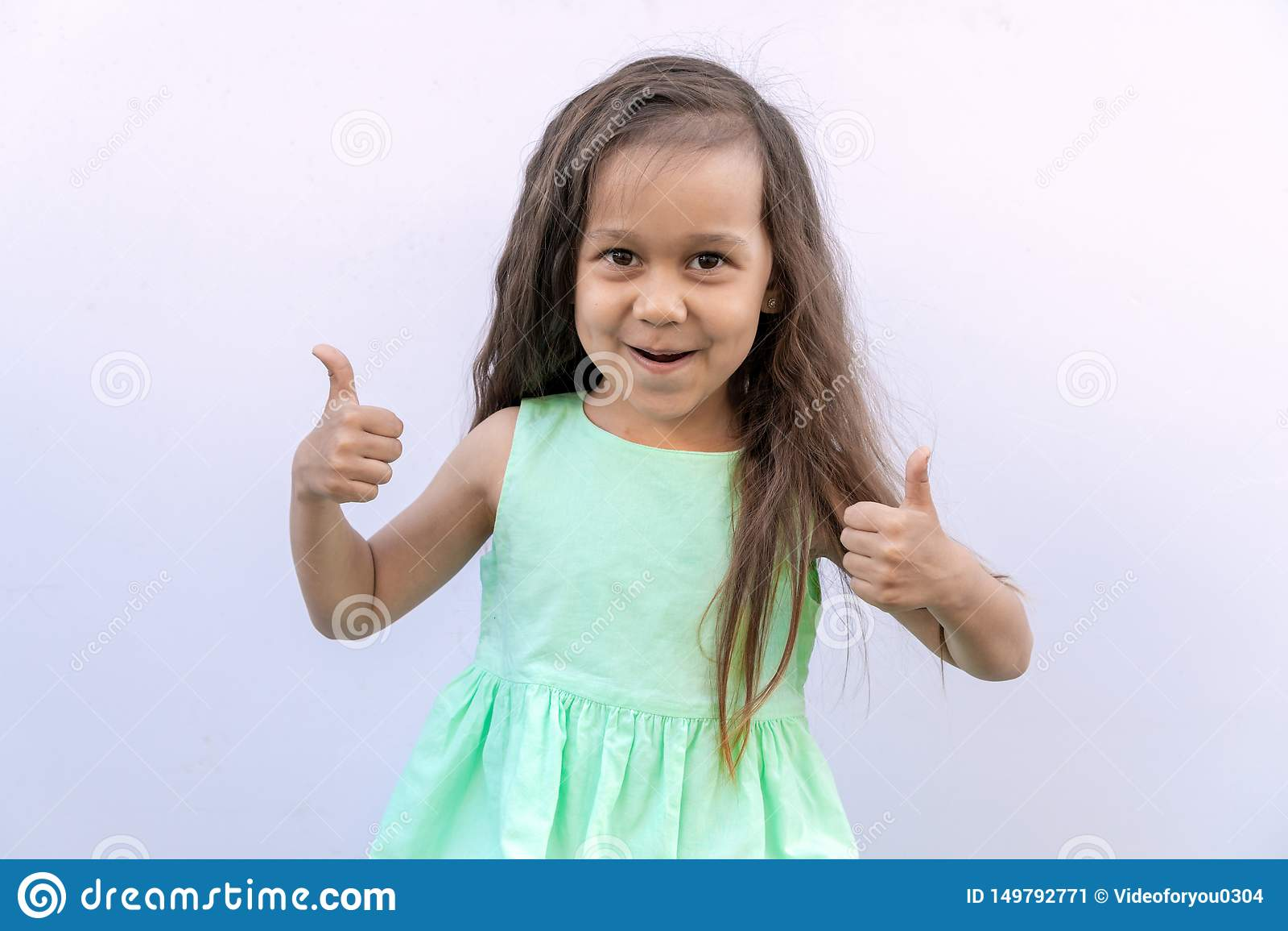 Bambina con capelli ricci lunghi marroni isolati su fondo bianco Bambino che d? due pollici su