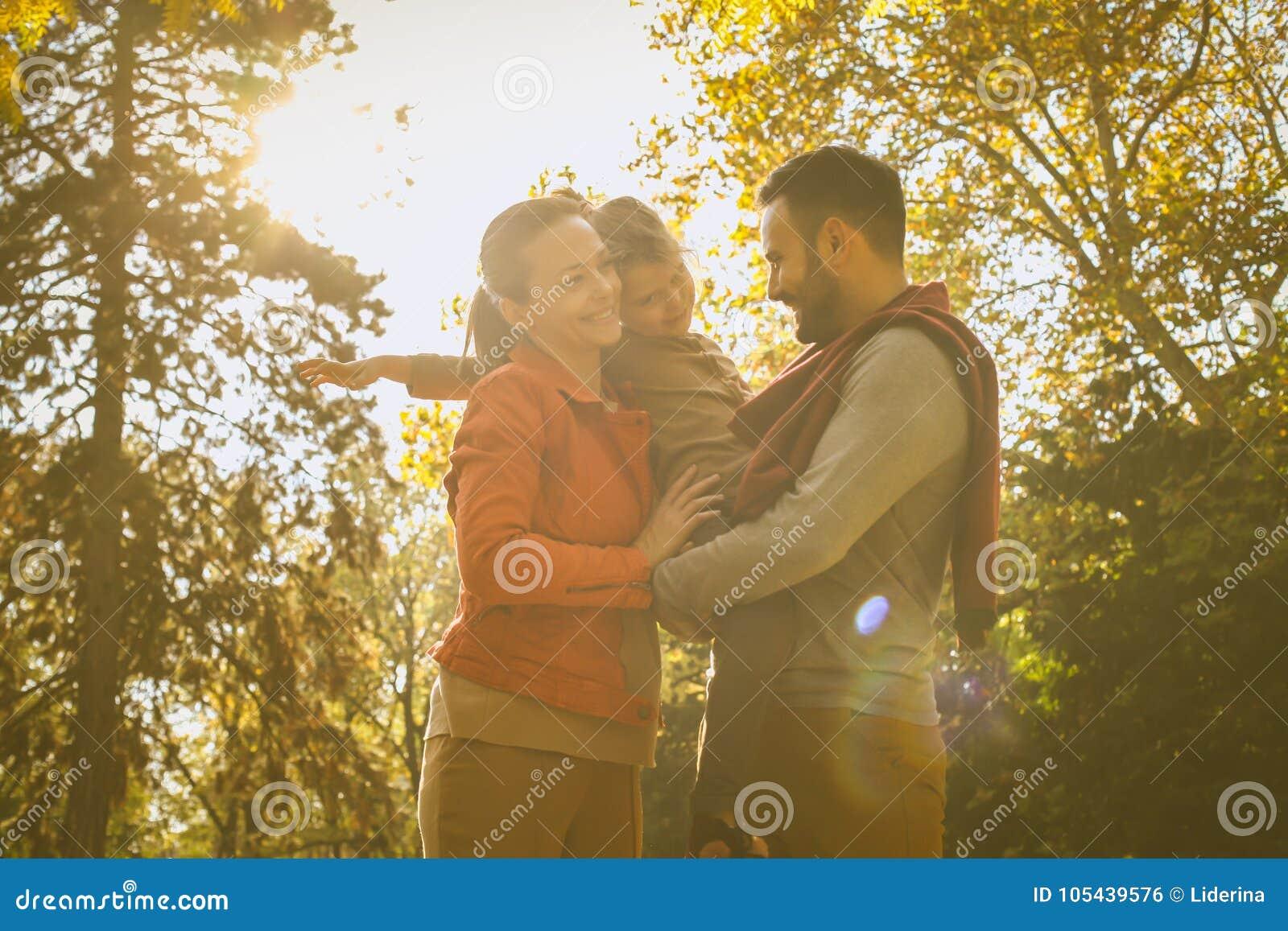 Bambina con i genitori al parco della città godere