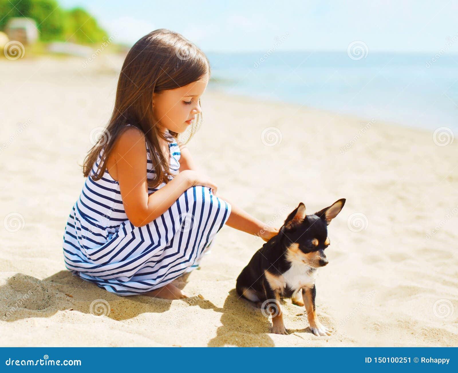 Bambina del ritratto di estate con il cane che si siede insieme