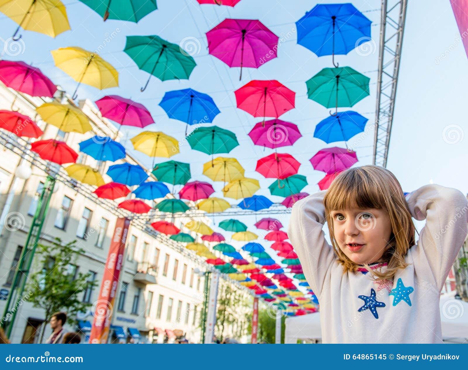 Bambina del ritratto nella via decorata con gli ombrelli colorati