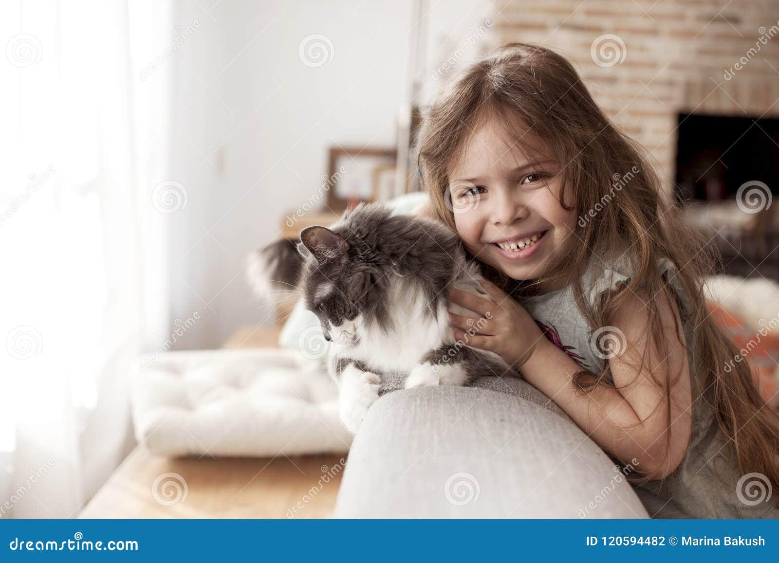 Bambina e gatto a casa sullo strato Un bambino felice e un animale domestico Copi lo spazio