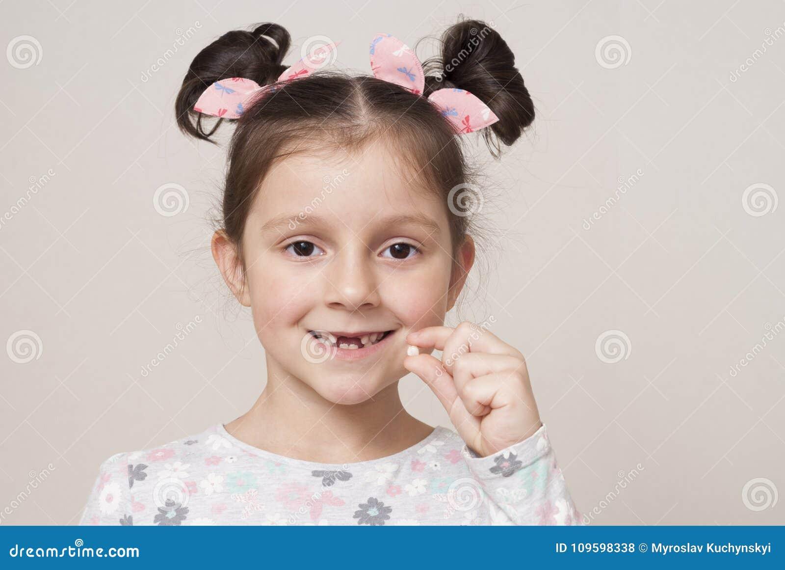 Bambina e un dente di latte