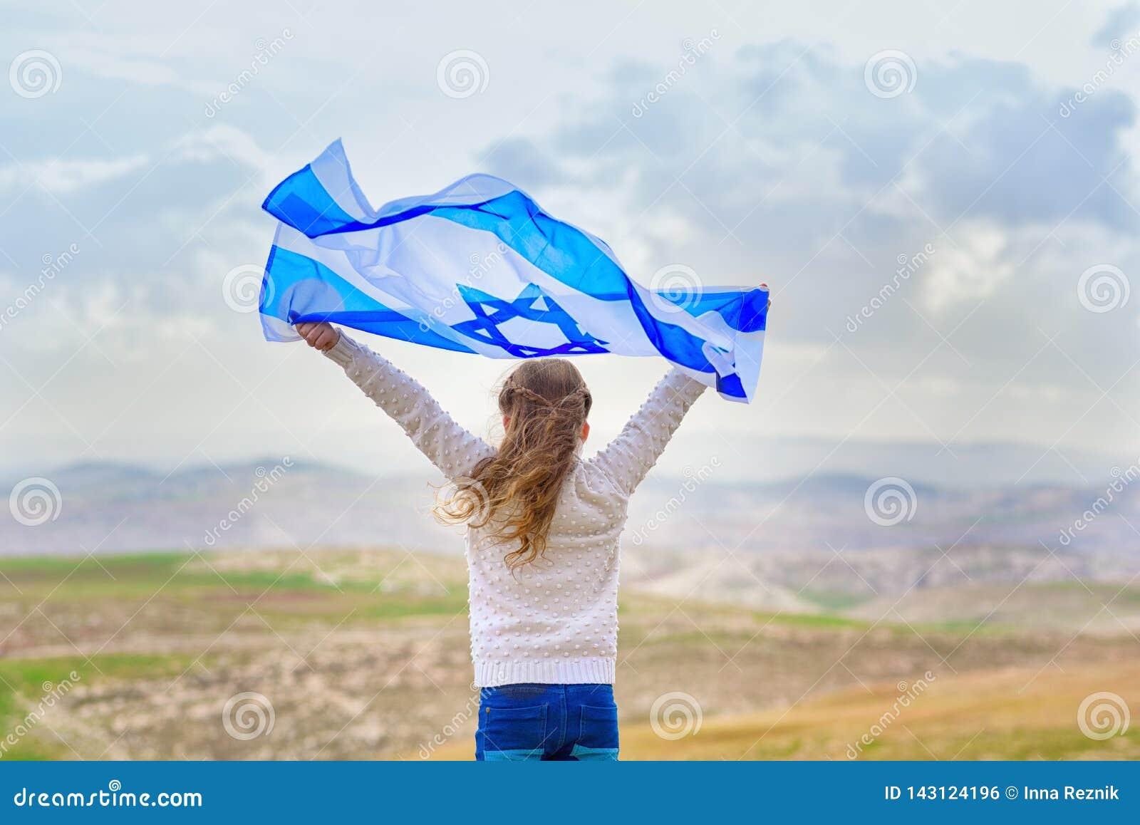 Bambina ebrea israeliana con la vista posteriore della bandiera di Israele