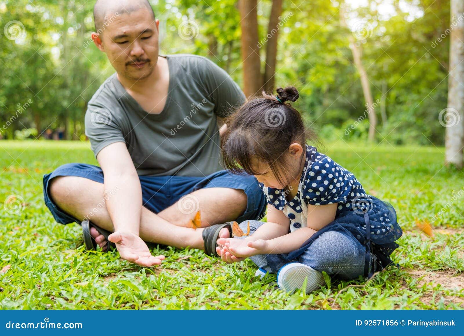 Bambina ed suo padre che esaminano le farfalle