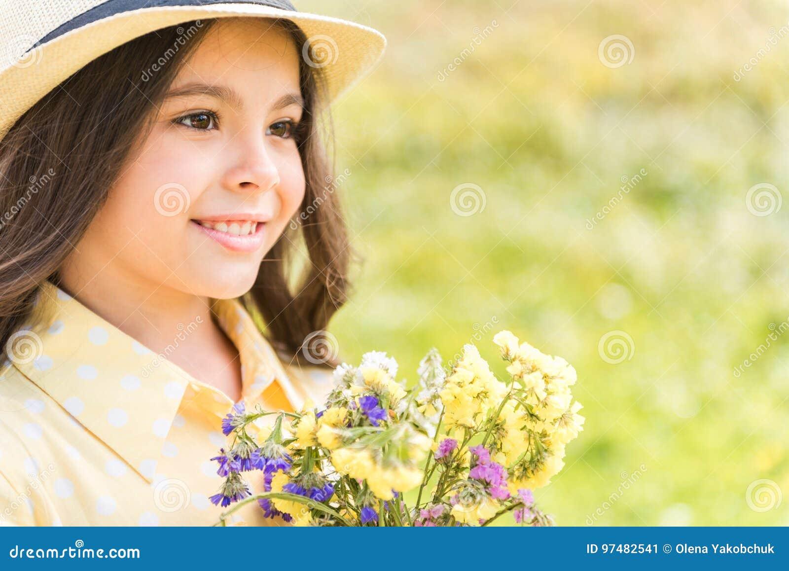 Bambina emozionante con i wildflowers sul campo