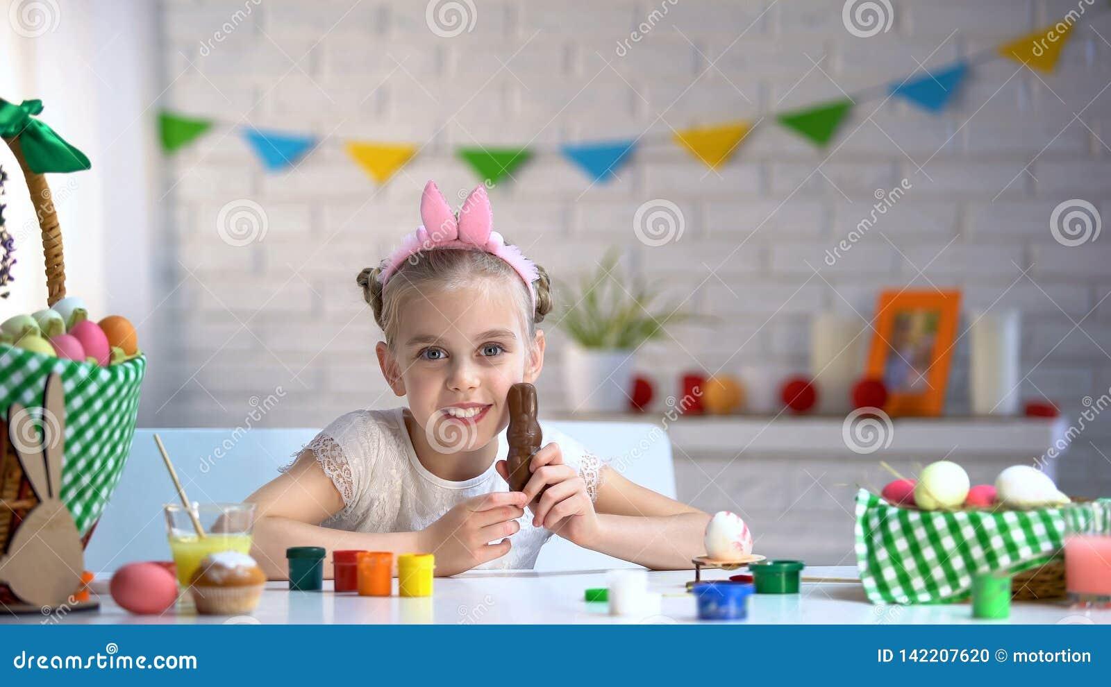 Bambina in fascia sveglia che sorride e che posa per la macchina fotografica con il coniglietto del cioccolato