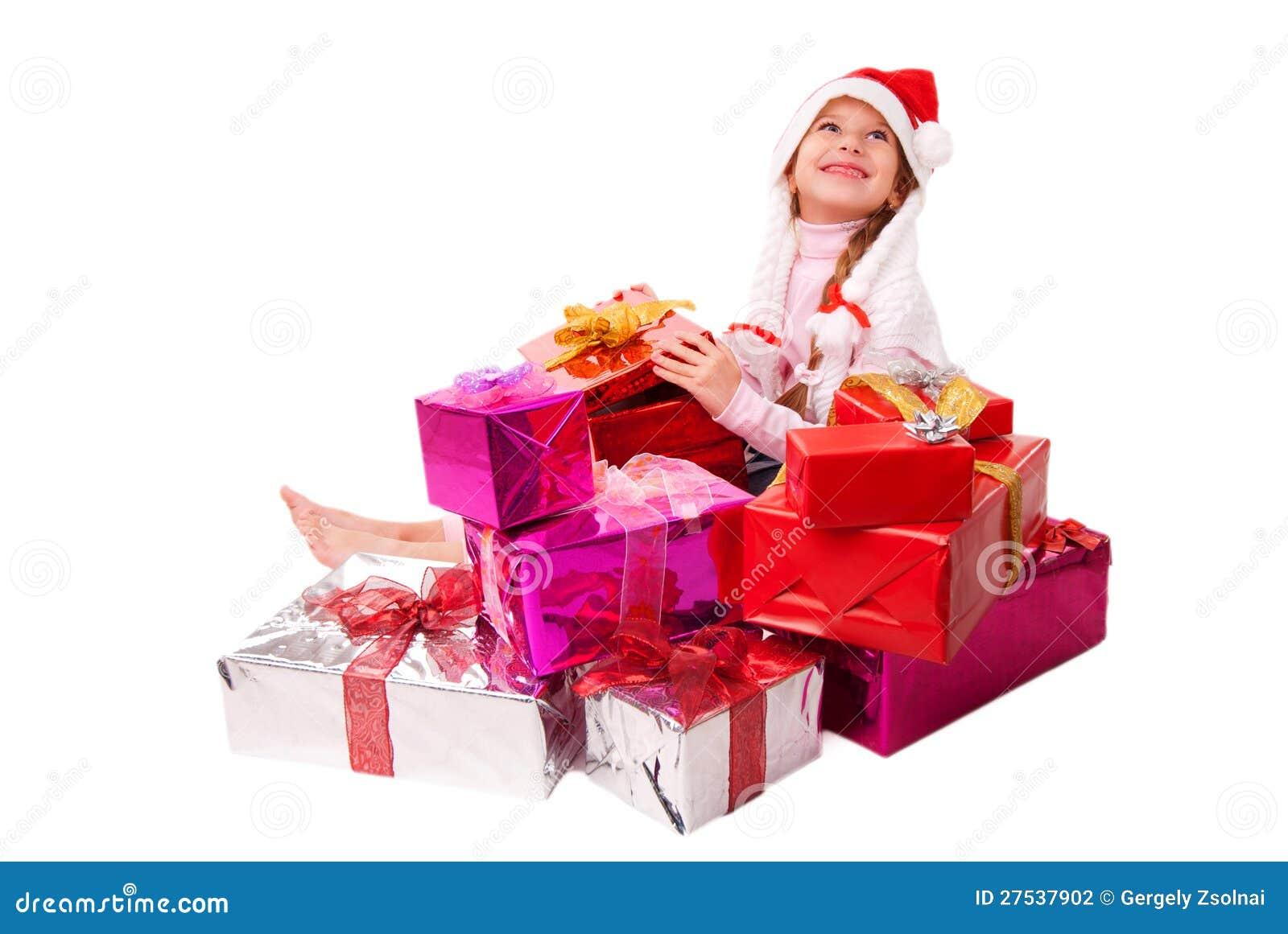 Bambina felice che si siede sui contenitori di regalo