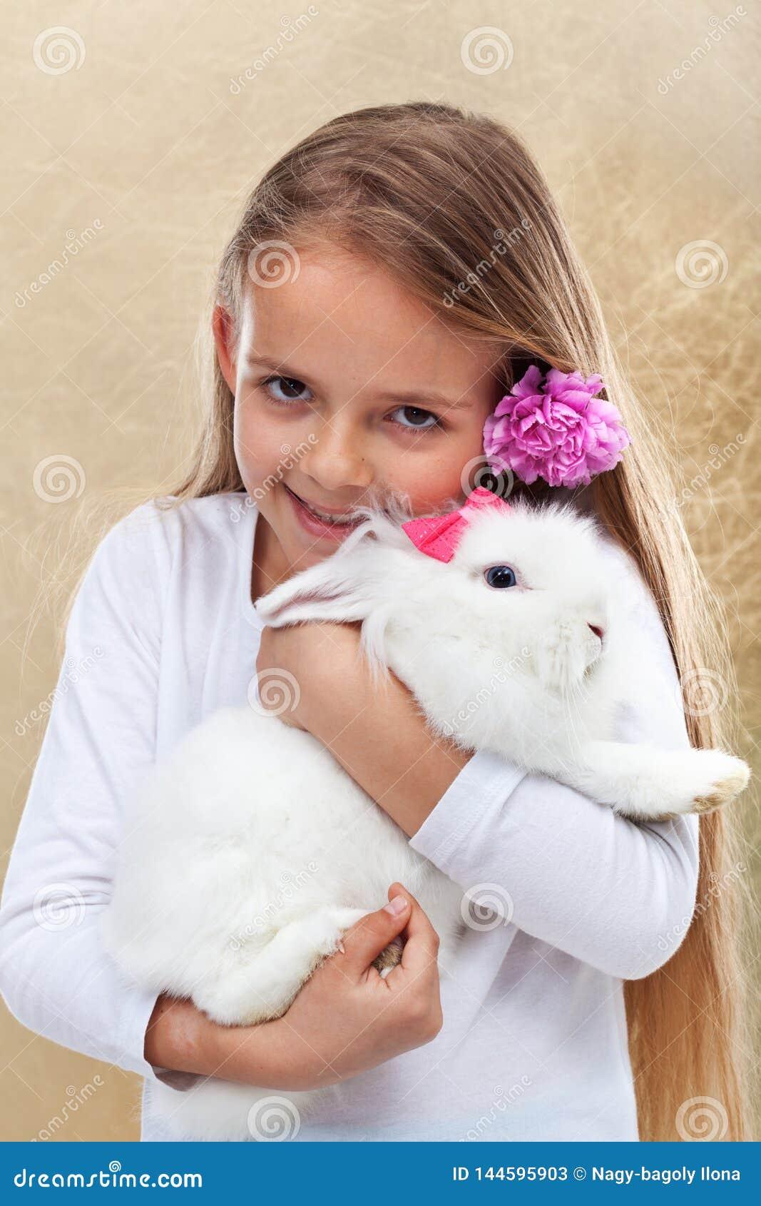 Bambina felice che tiene il suo coniglio bianco sveglio