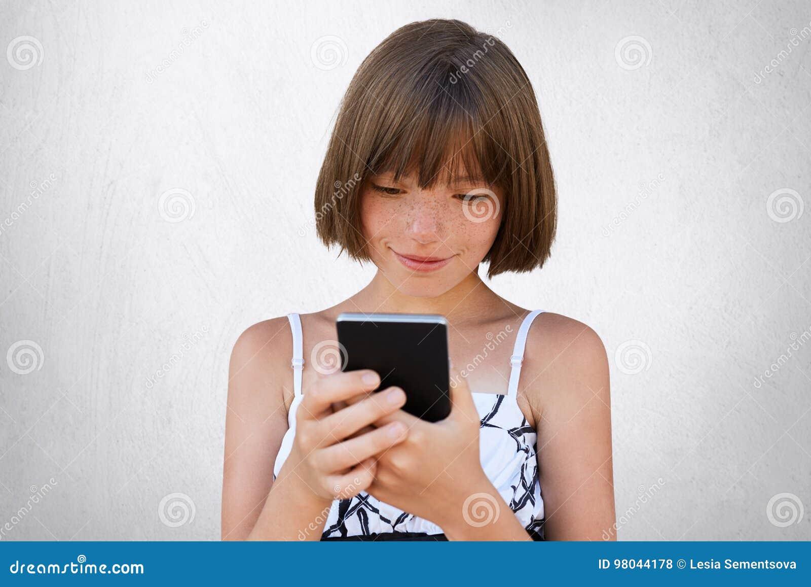 Bambina graziosa che esamina attentamente il suo Smart Phone mentre guardando i fumetti online facendo uso del collegamento a Int