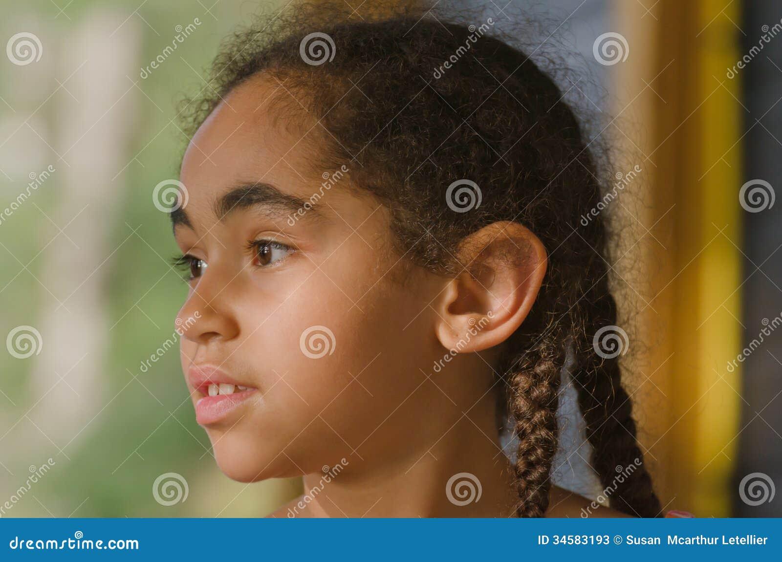 Bambina graziosa che fissa fuori