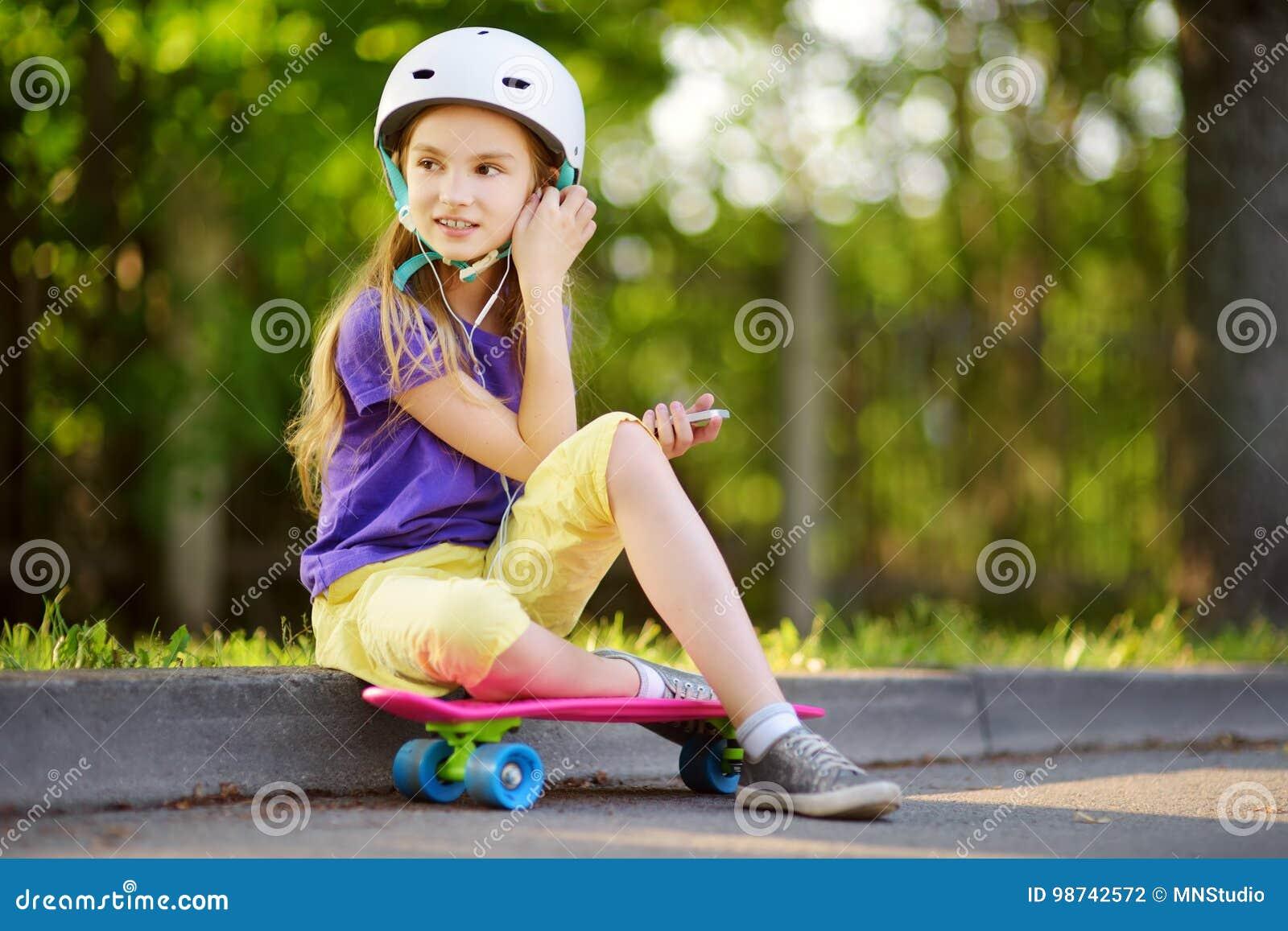 Bambina graziosa che impara pattinare il bello giorno di estate in un parco Bambino che gode del giro pattinante all aperto