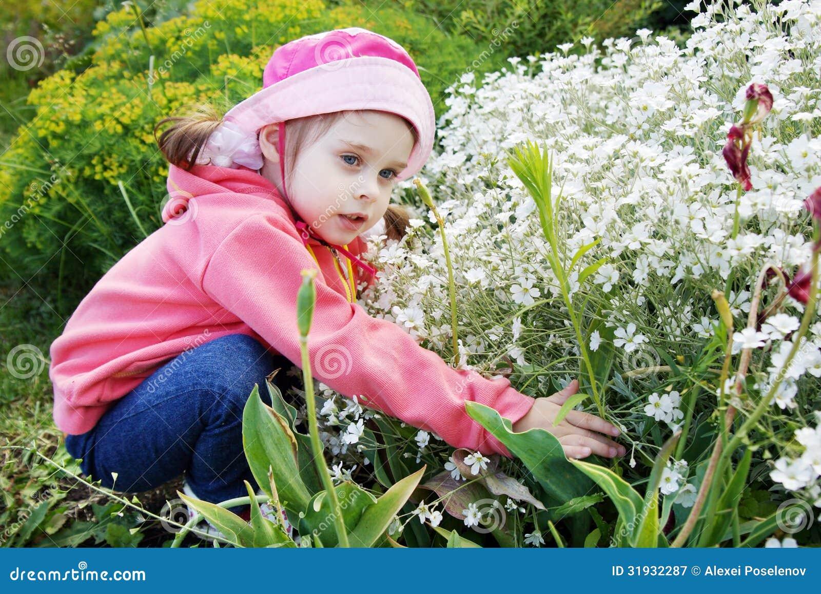 Bambina graziosa in un giardino con i fiori bianchi for Giardino con fiori