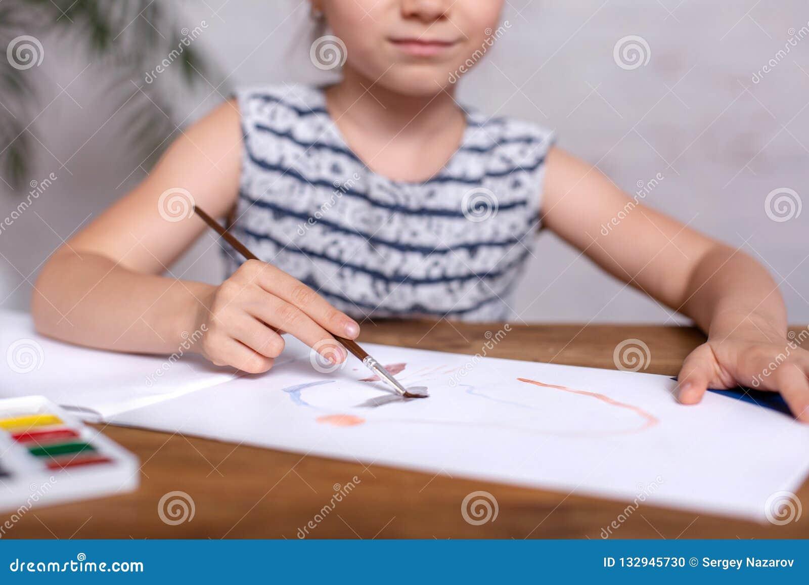 Bambina ispirata al tiraggio della tavola con le pitture Primo piano