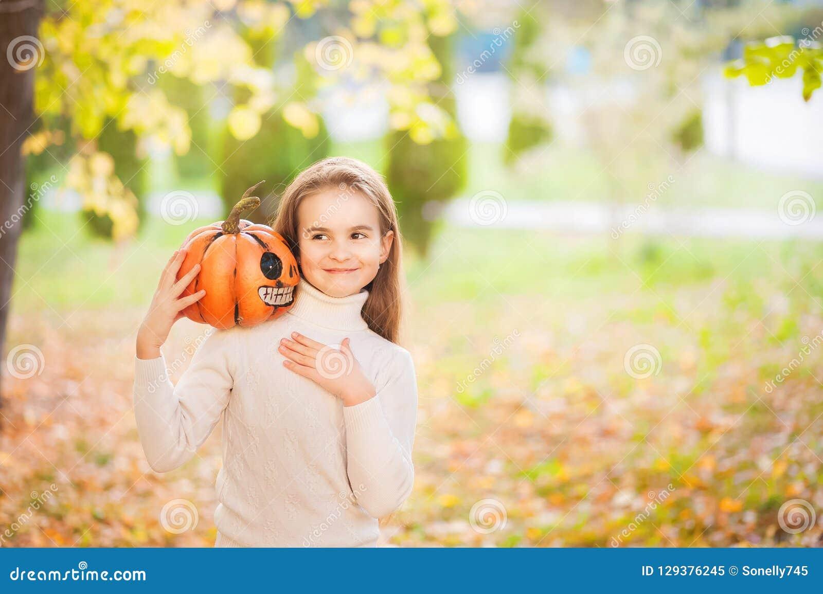Bambina in maglione bianco e jeans su un fondo di sfondo naturale strutturale verde Una ragazza bisbiglia in suo orecchio un segr