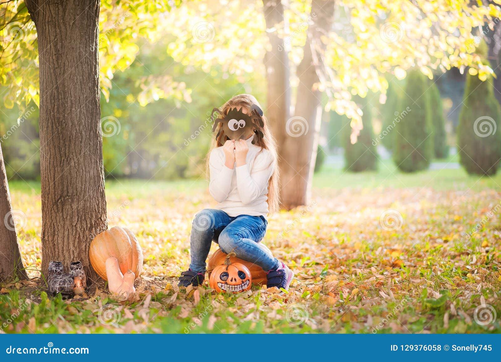 Bambina in maglione bianco e jeans su un fondo di sfondo naturale strutturale verde Una ragazza si siede sulle zucche e sulle cop