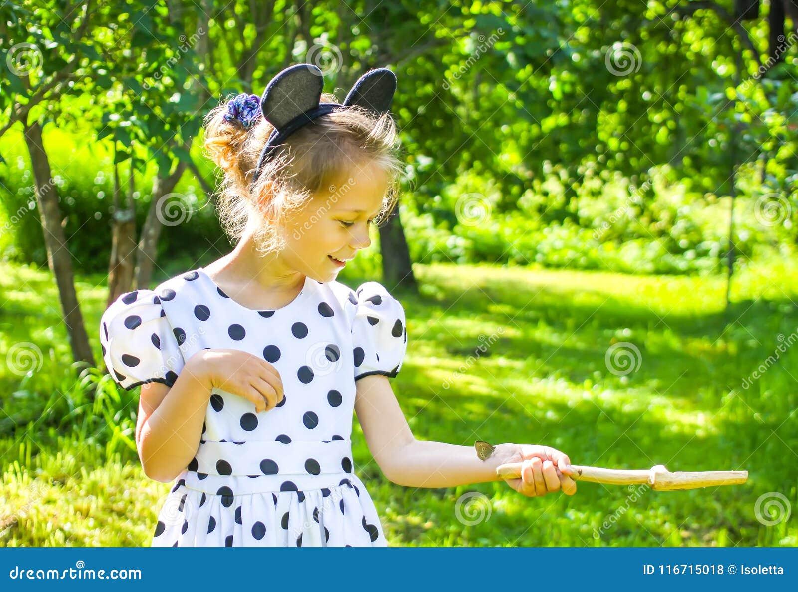 Bambina nel parco di estate con la piccola farfalla che si siede sulla sua mano