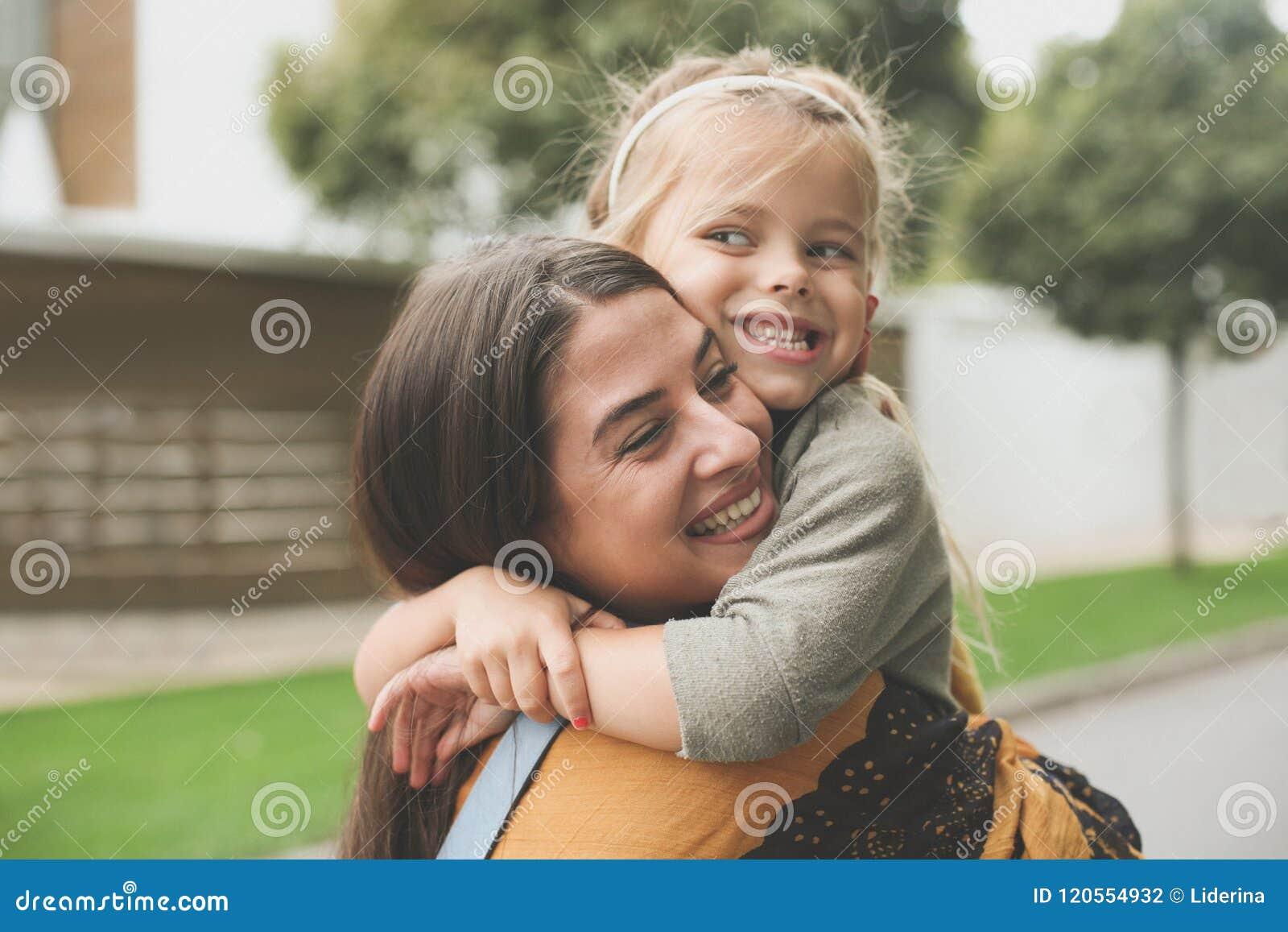 Bambina nell abbraccio delle mamme