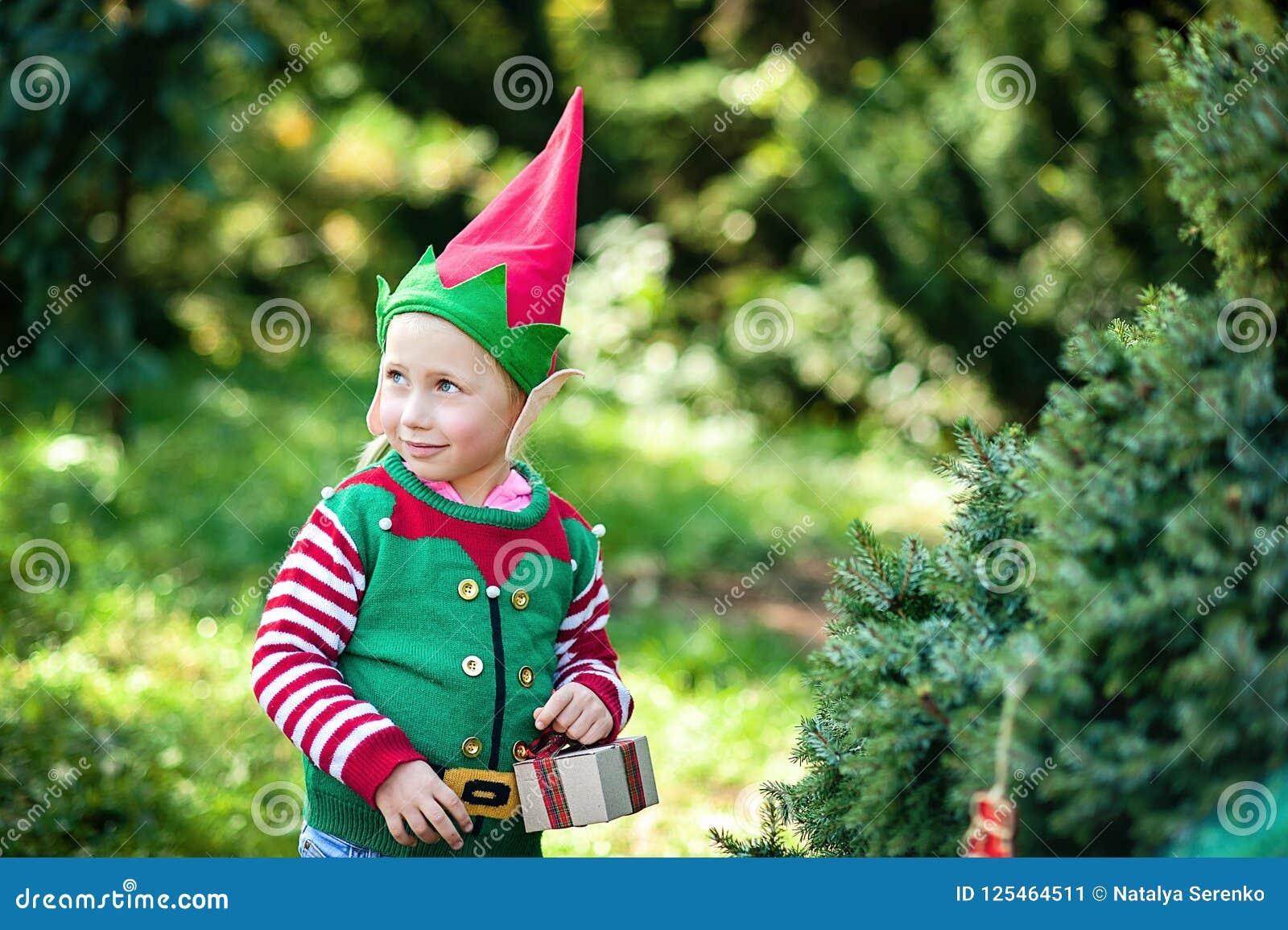 Bambina nell aspettare del maglione e del cappello dell elfo Natale nel legno Ritratto di ritratto a mezzo busto di piccolo bambi