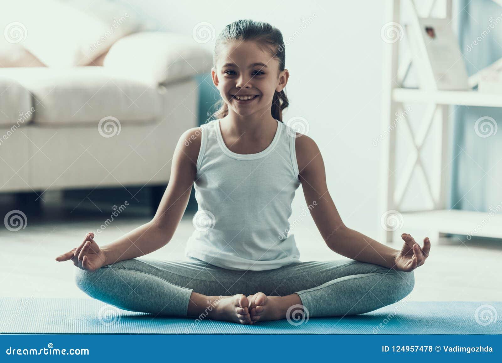 Bambina Che Fa Ginnastica Su Una Stuoia Verde Di Yoga