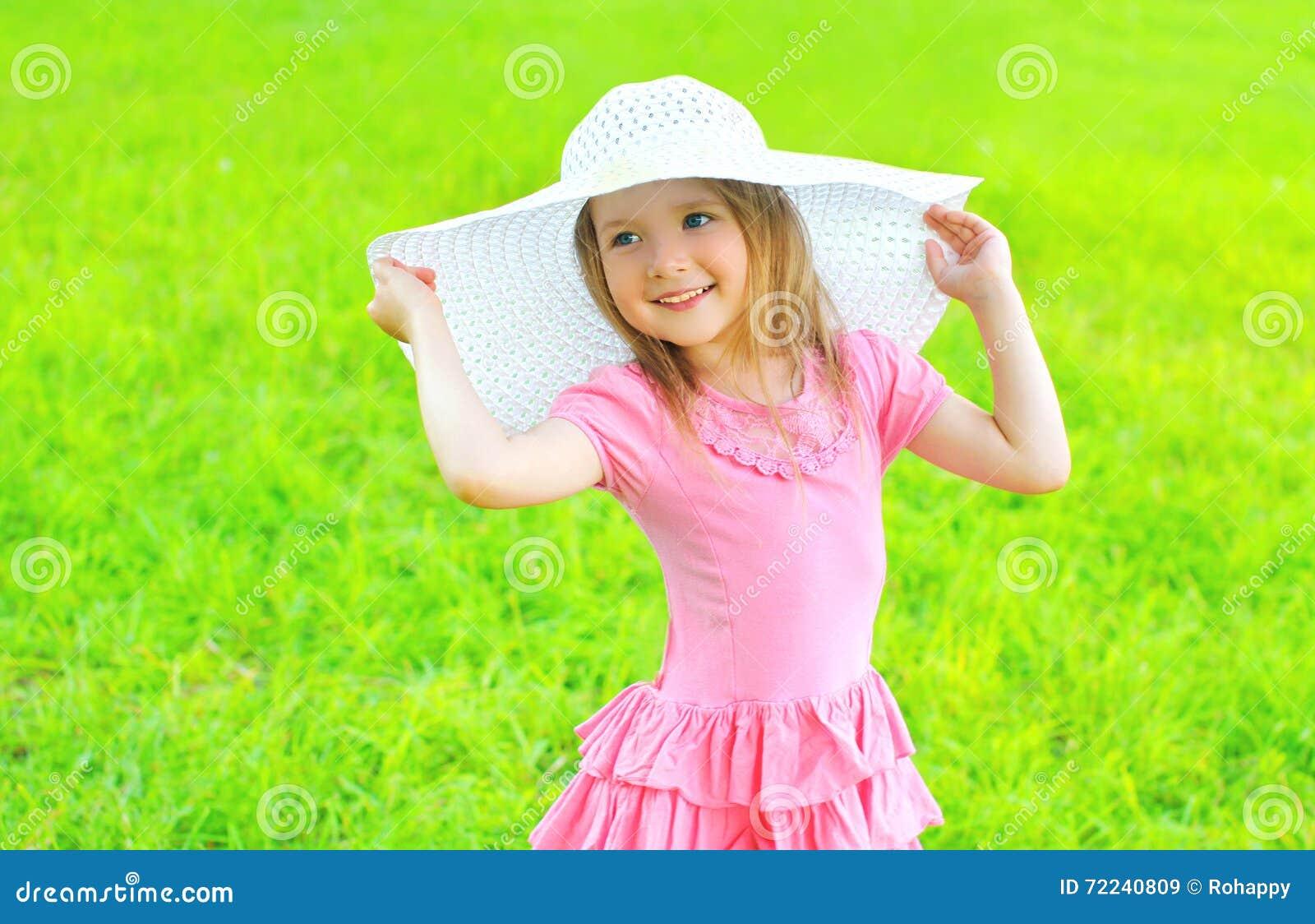 Bambina sorridente felice in cappello di paglia e del vestito all aperto