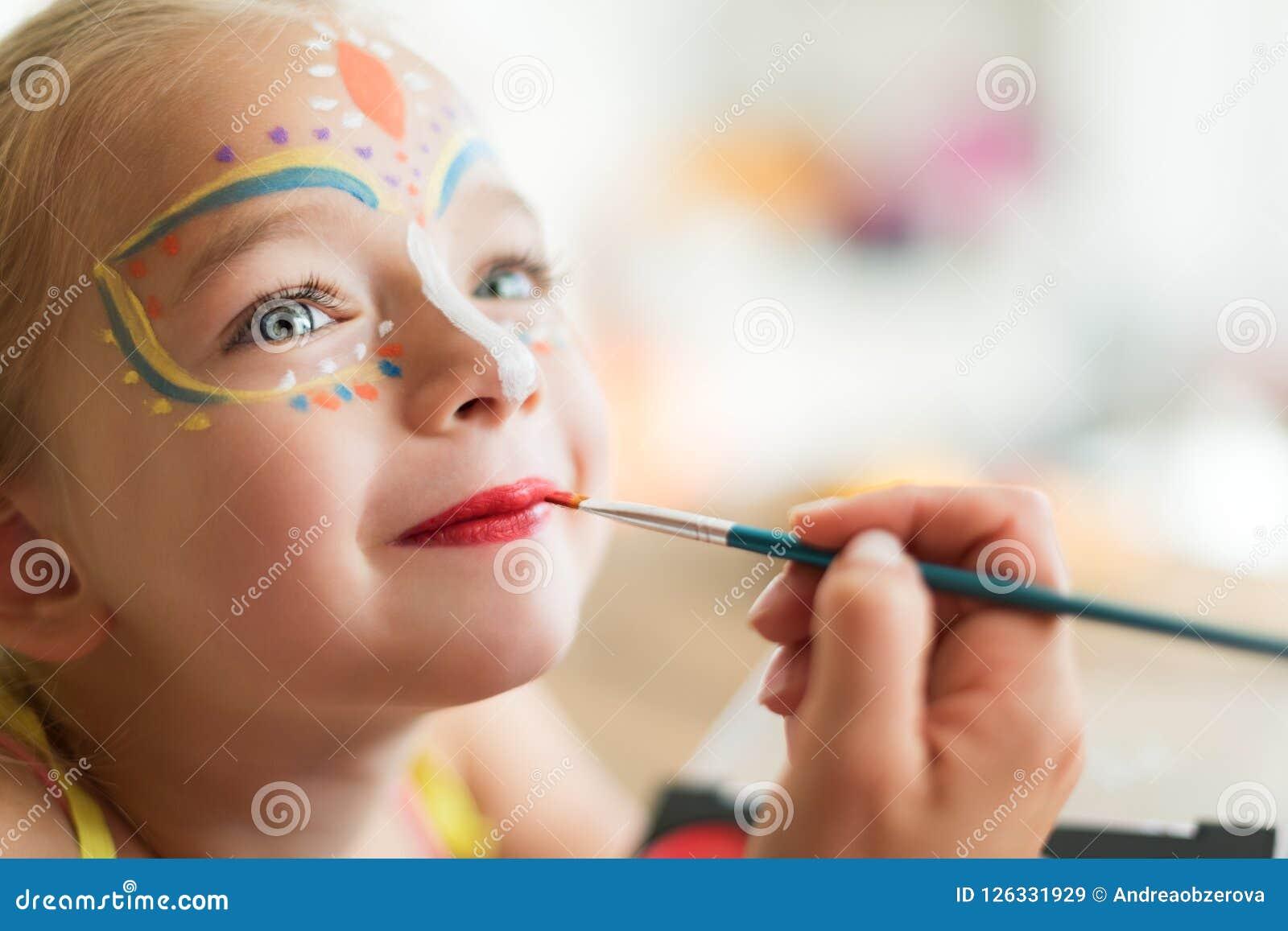 Bambina sveglia che fa il suo dipingere fronte per il partito di Halloween Fondo di stile di vita della famiglia di carnevale o d