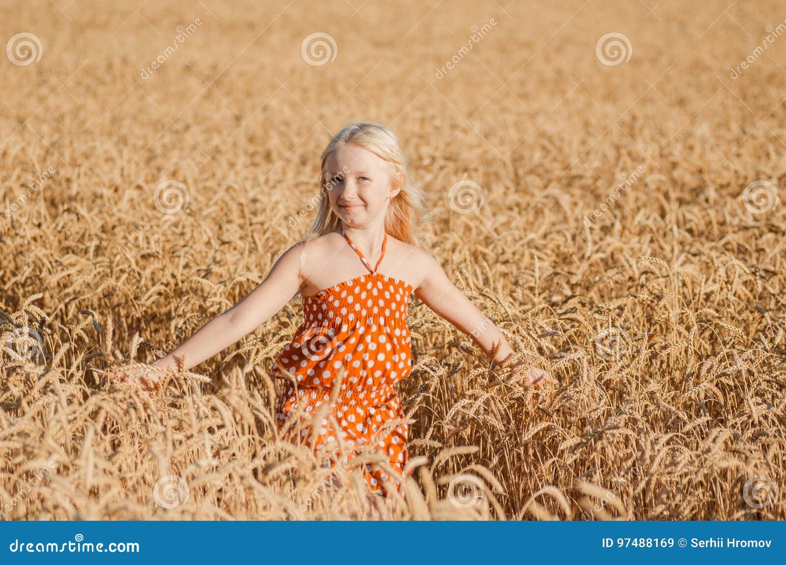 Bambina sveglia che gioca nel campo di estate di grano