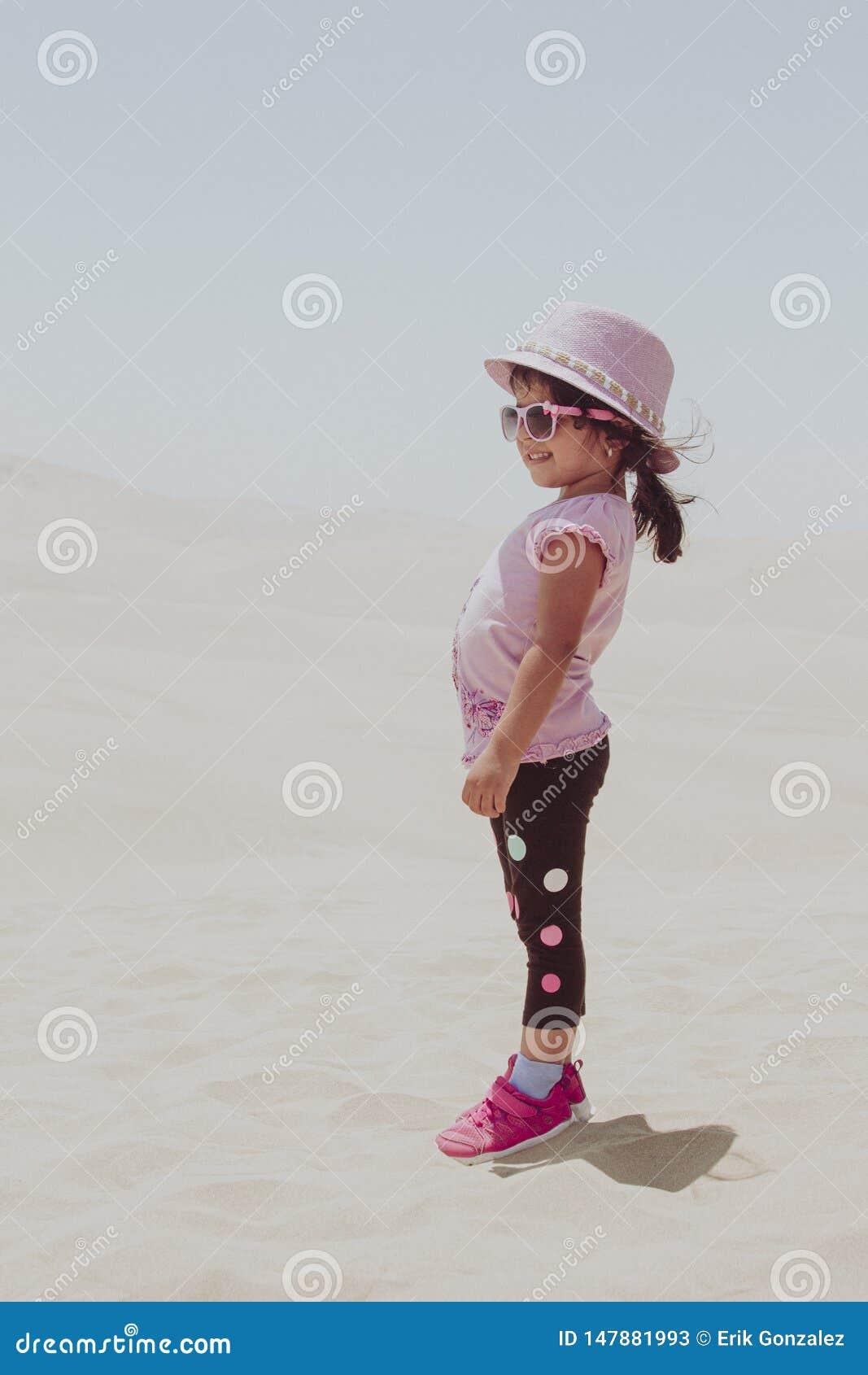 Bambina sveglia che gioca nelle dune