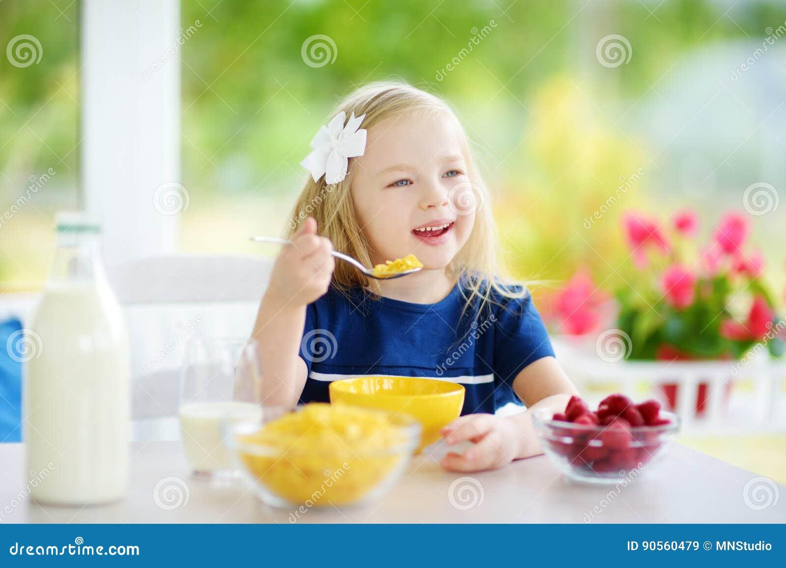 Bambina sveglia che gode della sua prima colazione a casa Bambino grazioso che mangia i fiocchi di mais ed il latte alimentare e