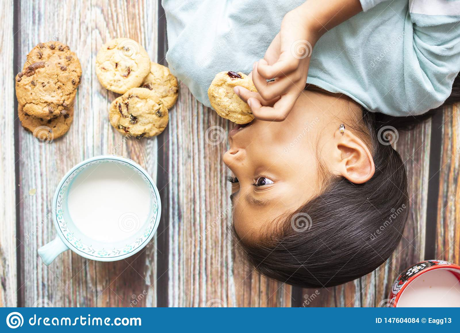 Bambina sveglia che mangia i biscotti con latte