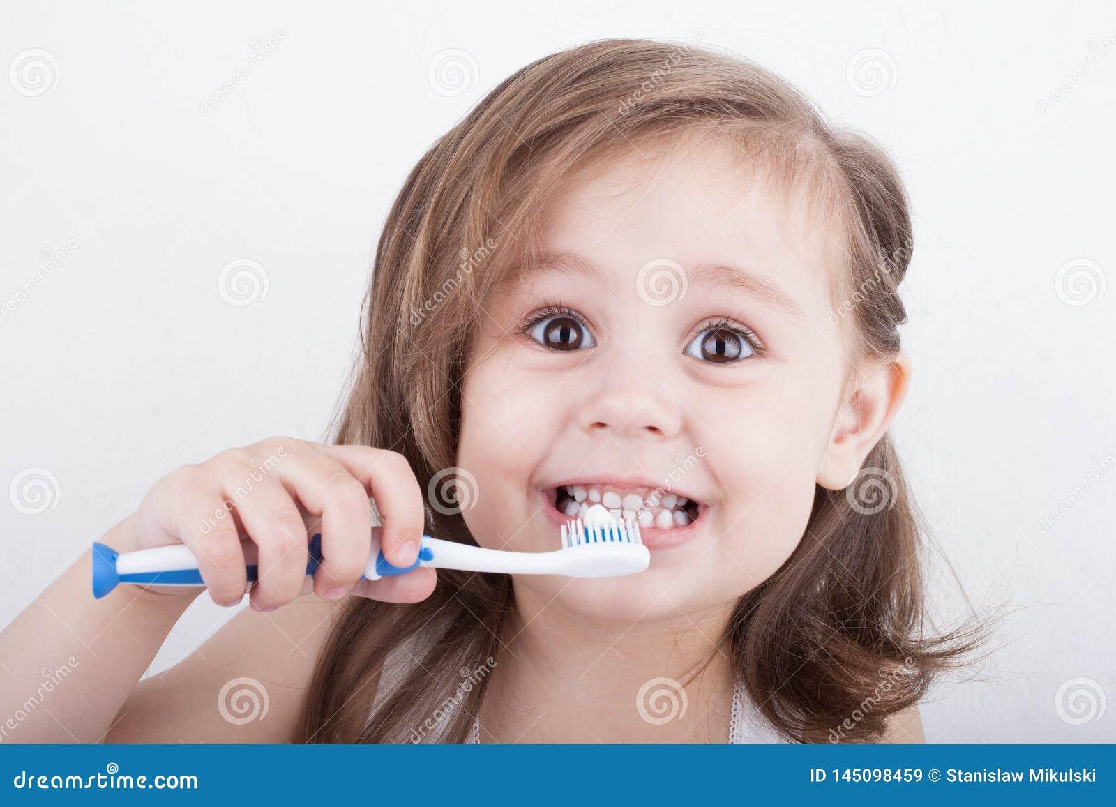 Bambina sveglia che pulisce i suoi denti