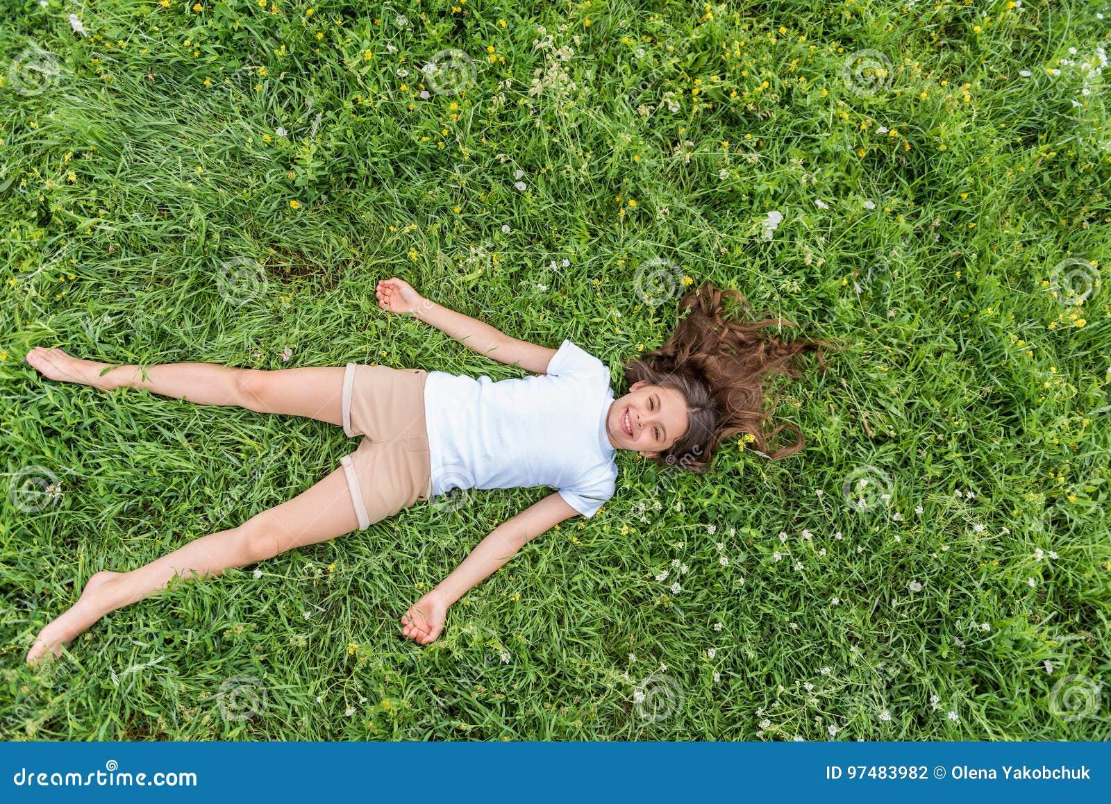 Bambina sveglia che si rilassa sull erba di estate