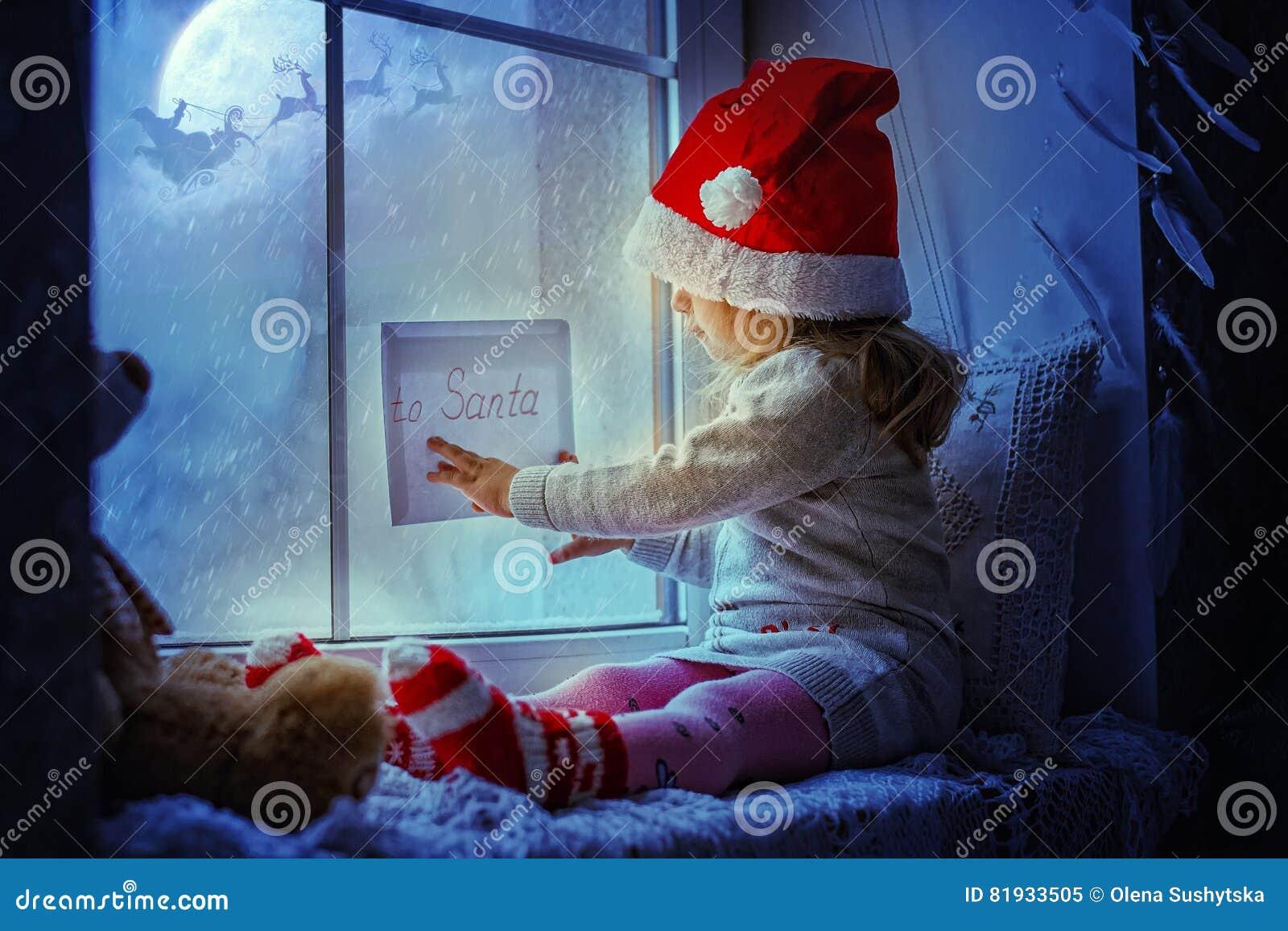 Bambina sveglia che si siede dalla finestra con una lettera a santa claus immagine stock - Finestra che non si chiude ...