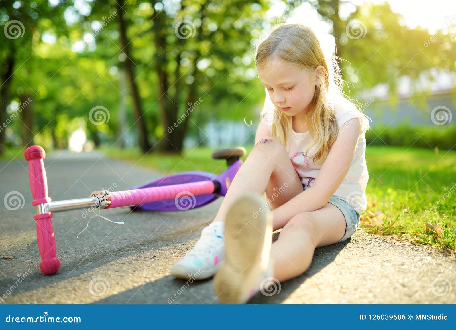 Bambina sveglia che si siede sulla terra dopo la caduta fuori il suo motorino al parco di estate Bambino che ottiene ferita mentr
