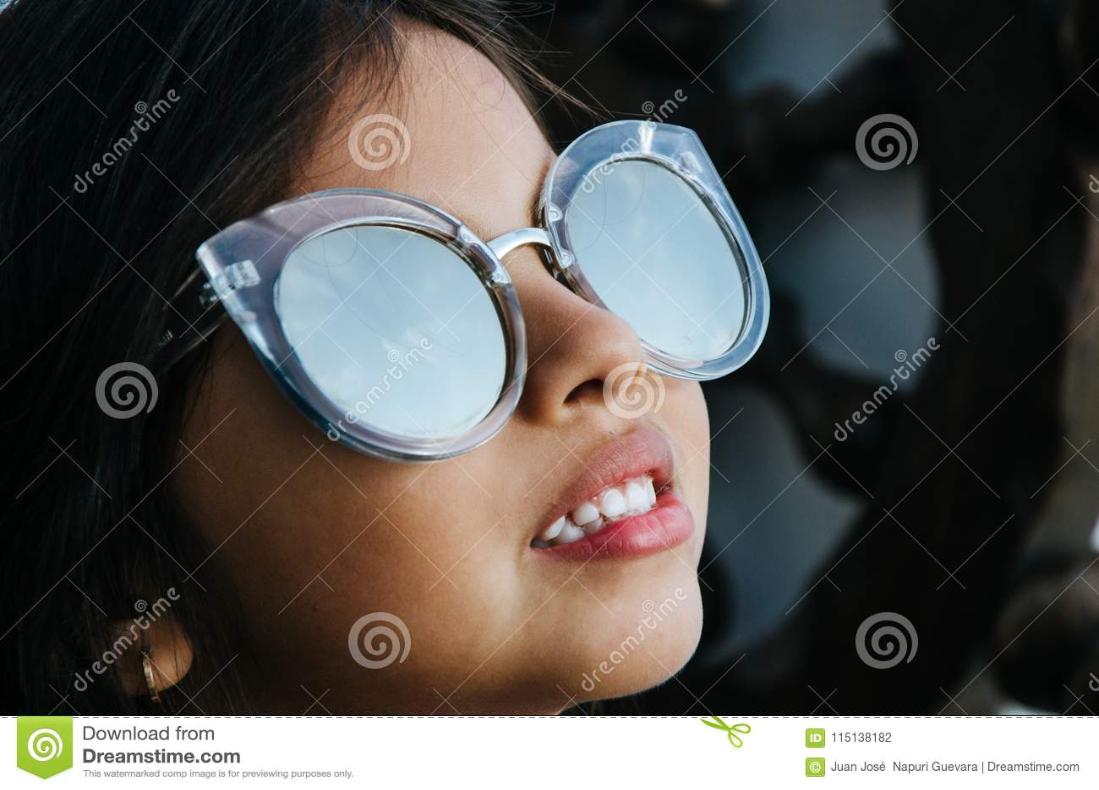 Bambina sveglia che sorride con gli occhiali da sole