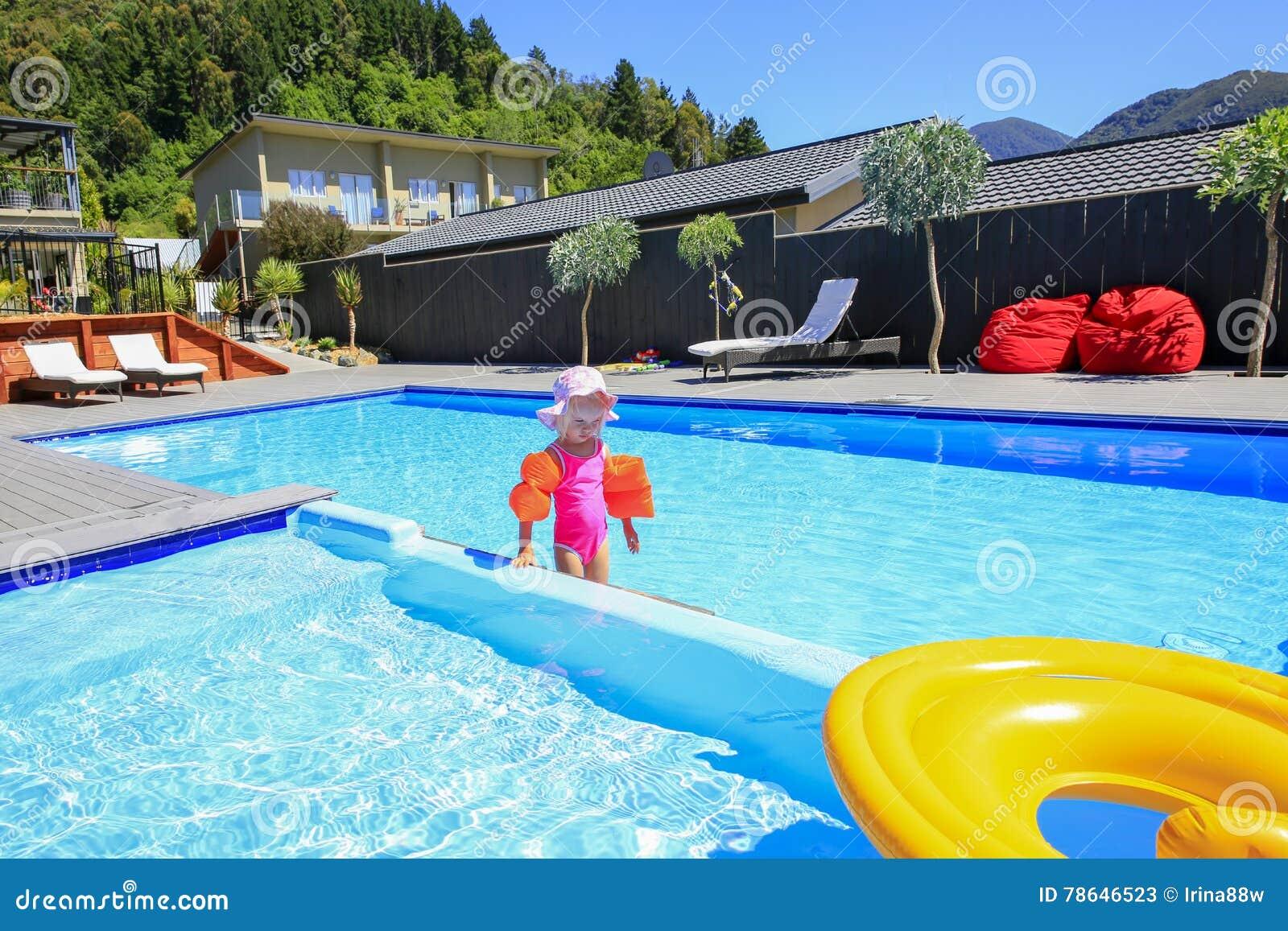 Bambina sveglia in un costume da bagno rosa che cammina in una piscina blu immagine stock - Borsone piscina bambina ...